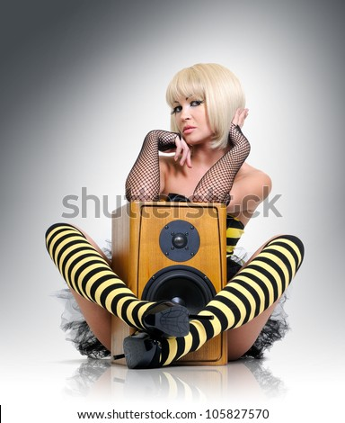 Glamorous sexy young girl with wooden speaker, sound concept - stock photo