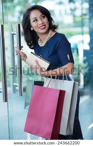 Glamorous Vietnamese woman with clutch and shopping bags leaving the store