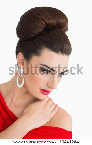 Glamorous woman looking down while wearing a red dress - stock photo