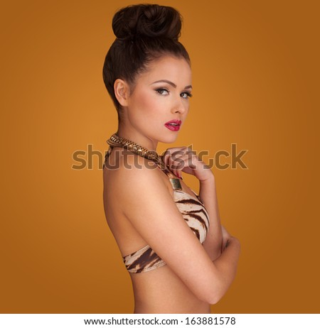 Glamorous woman with a friendly smile in a stylish outfit wearing her hair in a bun standing sideways on a yellow studio background - stock photo