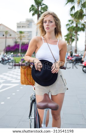 Glamorous young attractive woman resting after riding on her classic bicycle in urban setting, stylish modern female posing for the camera while standing with her retro bike in street on cloudy day  - stock photo