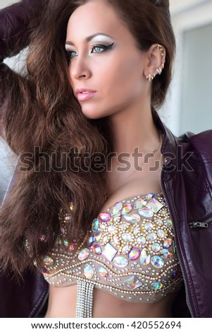 Glamorous young brunette woman in purple leather jacket and sparkly bra with beautiful makeup - stock photo