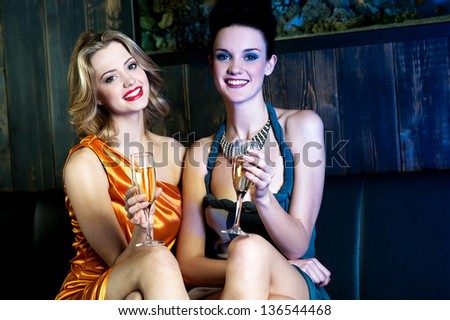 Glamorous young girls enjoying wine at nightclub, posing legs crossed. - stock photo