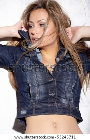 Glamorous young sexy woman near white wall - stock photo