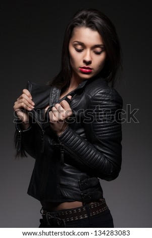 Glamorous young woman in black leather jacket on dark background