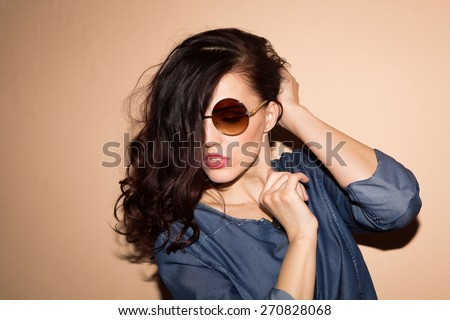 Glamorous young woman in jeans clothes studio