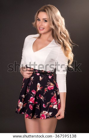 Glamorous young woman in short dress on dark background - stock photo