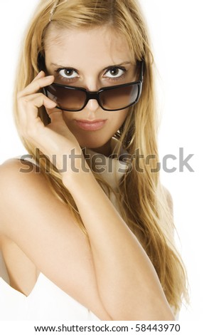 Glamorous young woman looking over the top of her modern sunglasses