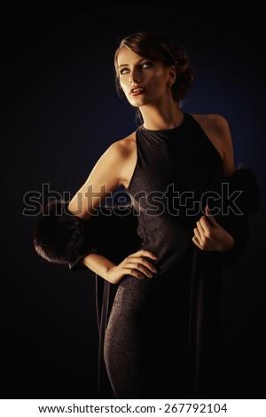 Glamorous young woman wearing black evening dress posing over black background. Luxury. Beauty, fashion. Make-up.   - stock photo