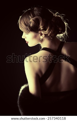 Glamorous young woman wearing black evening dress standing back over black background. Luxury. Beauty, fashion. Make-up.   - stock photo
