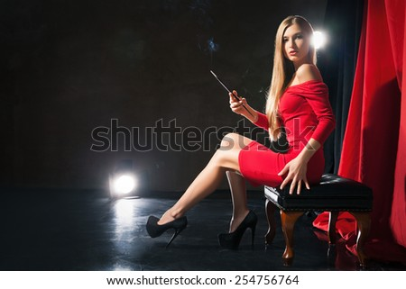 Glamorous young woman  with cigarette wearing red dress sitting on a stool on stage hand on hip.  - stock photo