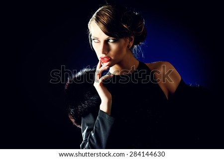 Glamorous young woman with evening make-up over dark background. Luxury. Beauty, fashion. Make-up.   - stock photo