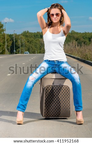 Glamour beautiful girl with a suitcase on the road posing - stock photo