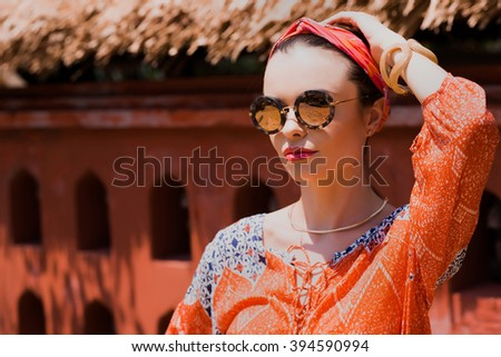 Glamour beautiful young sexy woman in sunglasses is posing near the orange wall