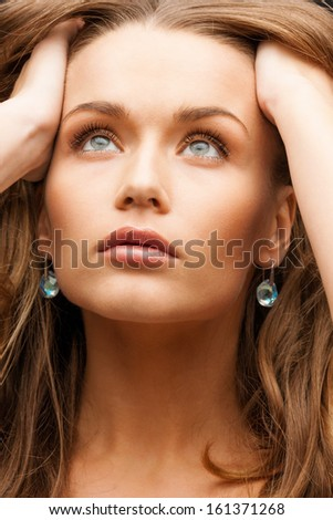 glamour, beauty and health, concept - beautiful calm woman with beautiful earrings holding head and looking up - stock photo