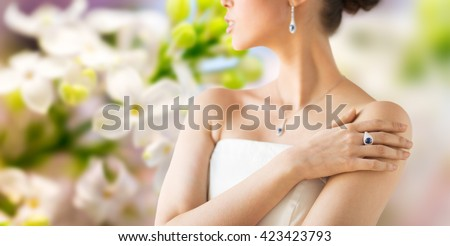 glamour, beauty, jewelry and luxury concept - close up of beautiful woman with finger ring over natural spring lilac blossom background