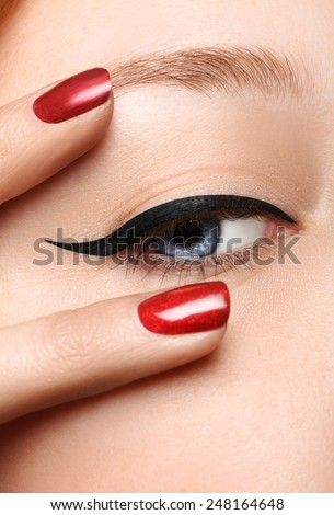 Glamour black arrow makeup close with fashion red nails on face. Woman with perfect skin. Macro shot. Half-closed eye - stock photo