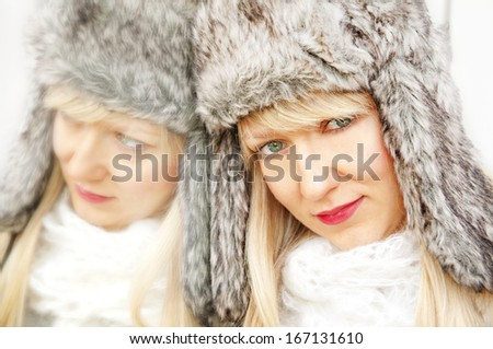 Glamour blonde girl in a furry hat smiling next to a mirror