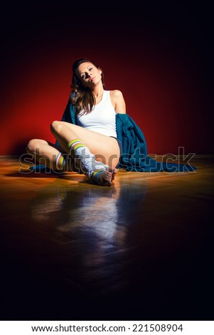 Glamour brunette sitting on the wooden floor - stock photo