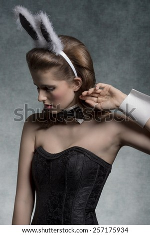 glamour easter shoot of sexy brunette woman with fluffy bunny ears, papillon and black corset, in fashion pose  - stock photo