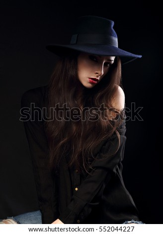 Glamour fashion female model posing in black shirt and elegant hat with red bright lipstick in dramatic light on dark shadow background