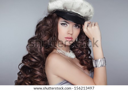 Glamour. Fashion girl  Model with long wavy healthy hair styling wearing in Cap isolated on grey background. Bright Makeup
