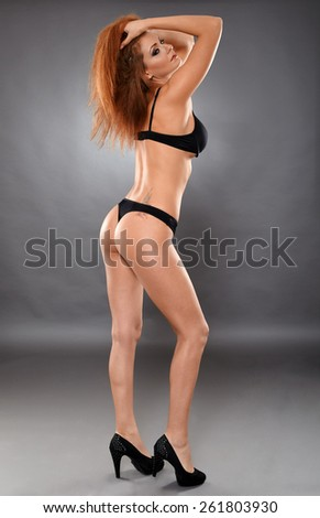 Glamour full length of a beautiful woman posing in black lingerie - stock photo