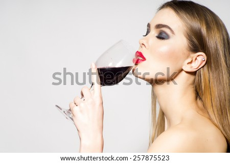 Glamour girl drinking red wine on white background