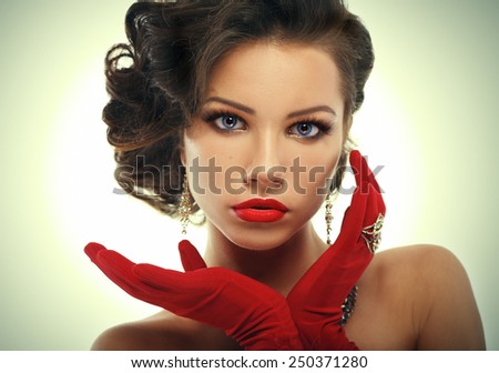 Glamour girl in red gloves holding hands near face. Vintage Style Mysterious Woman Wearing Red Glamour Gloves. - stock photo