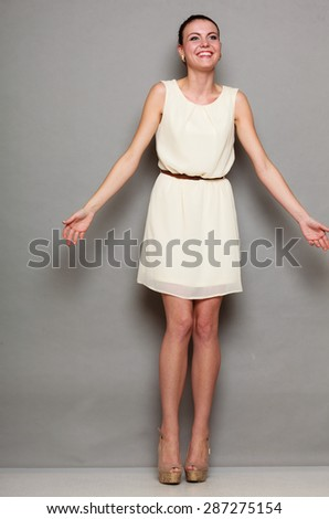 Glamour girl in white dress on gray. Fashion young slim woman posing in full length. Studio photo - stock photo