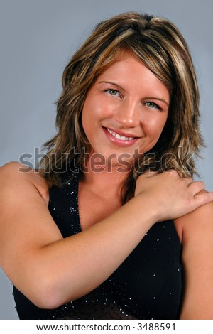 Glamour girl with black gown smiling over a neutral background.