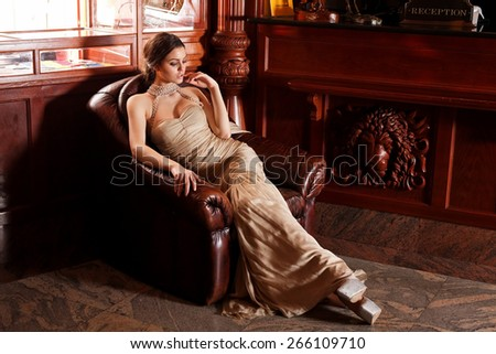 Glamour lady portrait in luxury dress. Beautiful model girl with perfect fashion makeup and hairstyle. Eelegant girl, in a luxury interior. - stock photo