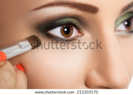 Glamour make up woman eye close up with make up brush. High-end Retouch - stock photo