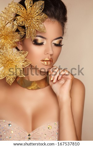 Glamour Makeup. Girl Face Close-up. Beauty Portrait Woman with golden flowers. Gold Jewelry. Hairstyle. Luxury photo - stock photo