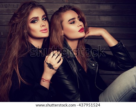 Glamour makeup two women with long hair style sitting on street wall background in dark light. Toned fashion closeup portrait