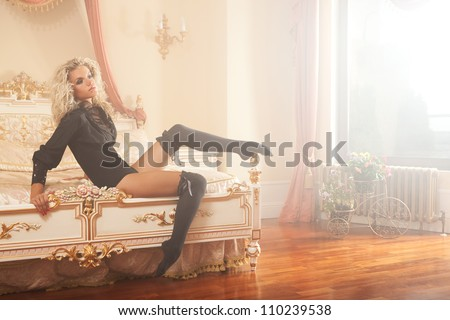 glamour picture of pretty girl in black lingerie laying on the bed in luxury interior - stock photo