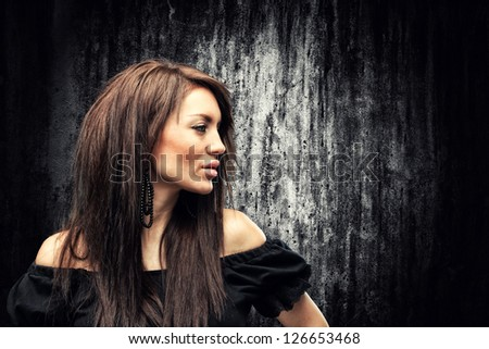 Glamour portrait of a beautiful young woman over concrete wall - stock photo