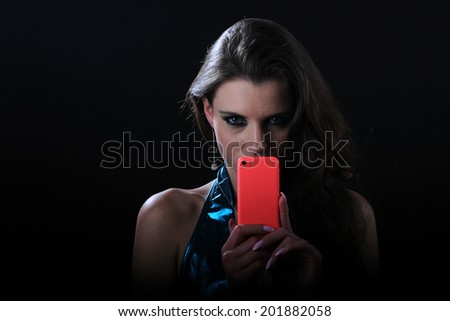Glamour portrait of a young and attractive woman holding her mobile phone. - stock photo