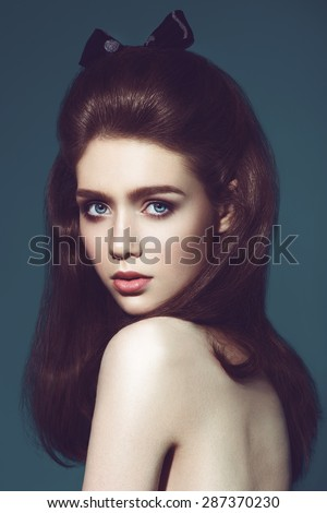 Glamour portrait of beautiful woman model with fresh daily makeup and funny wavy hairstyle. Fashion shiny highlighter on skin, sexy gloss lips make-up and natural eyebrows.dark background - stock photo