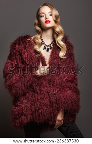 Glamour portrait of beautiful woman model with red lips and long blond hair in luxury fur coat color marsala - stock photo