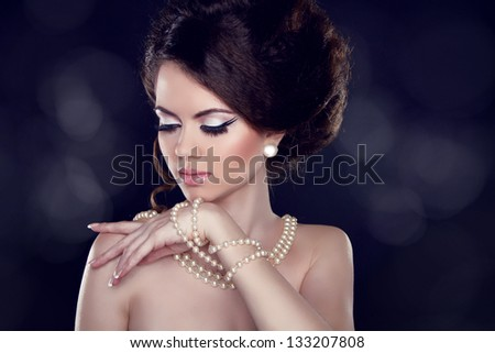 Glamour portrait of beautiful woman with pearl necklace on the bared shoulders - stock photo