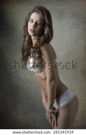 glamour portrait of provocative young woman with long natural  wavy hair, fashion bikini and jewellery. Fit body, erotic pose  - stock photo