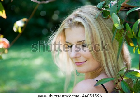 Glamour portrait of young beautiful spring woman in green garden near the tree - stock photo