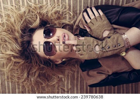 glamour sexy hot young woman with glasses & gloves lying on the couch crossed arms portrait - stock photo
