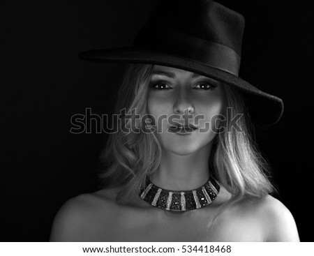 Glamour sexy makeup woman posing in fashion hat and gold necklace on dark background. Black and white art portrait. closeup