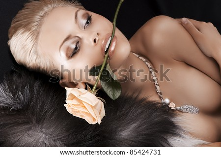 glamour shot of a sexy blonde laying on black wearing fur and a rose in her mouth - stock photo