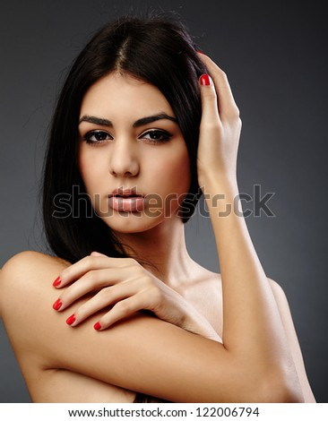 Glamour studio closeup portrait of an alluring young hispanic woman on gray background - stock photo