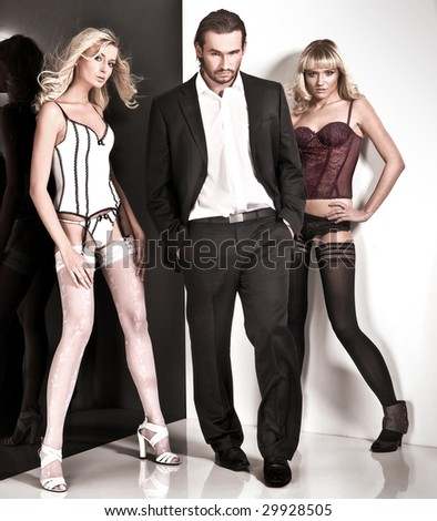 Glamour style studio shot of a man and 2 women - stock photo