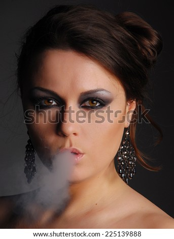 Glamour woman and cigarette smoke - stock photo