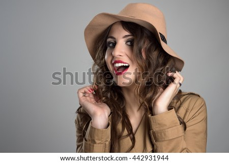 Glamour woman wearing hat adjusting and touching her hair looking at camera over gray studio background